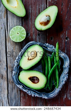 Top view of ripe halved avocados and green beans  on vintage metal plate - healthy food, diet or cooking concept. - stock photo