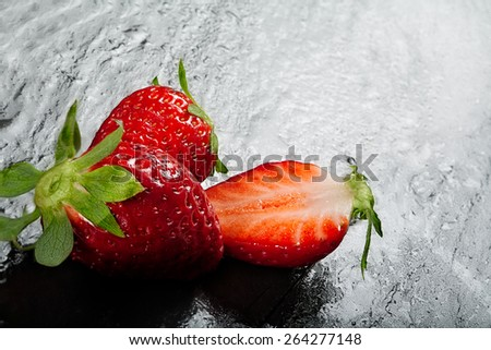 Top view of ripe red whole and halved succulent juicy strawberries on a slate background with copy space - stock photo