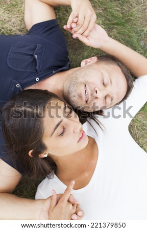 Top view of Romantic young couple holding hands relaxing with closed eyes outdoors in park on fresh green grass background Cute man and woman dreaming and sleeping outdoor Girl Face lie on shoulder