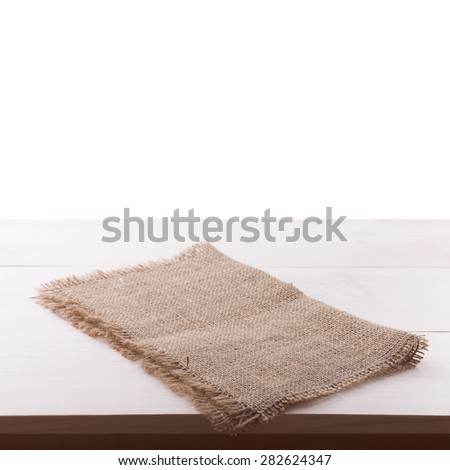 Top view of rough burlap napkin tablecloth on white wooden table isolated. Flat mock up for design.