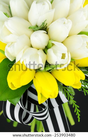 Top view of round tulip bouquet with striped black and white ribbon, perfect for a spring wedding and other festive occasions. - stock photo