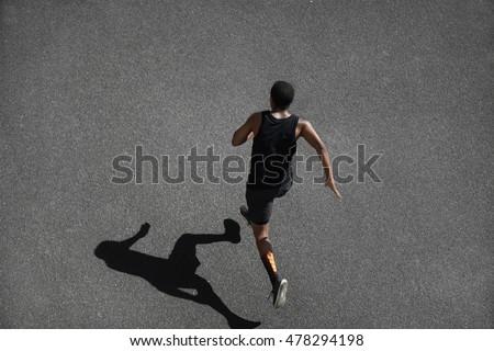 Athlete runner feet running on treadmill stock photo 373271314 top view of running man sprinting for success on run african muscular runner or jogger urmus Choice Image