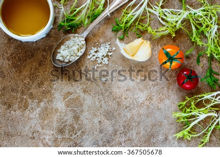 Top view of salad preparation with olive oil, herbs leaves, garlic and tomatoes on stone background with space for text.
