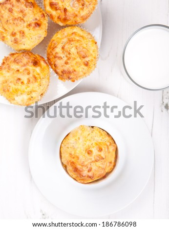 Top view of savory cheese and bacon muffins with milk on the white table - stock photo