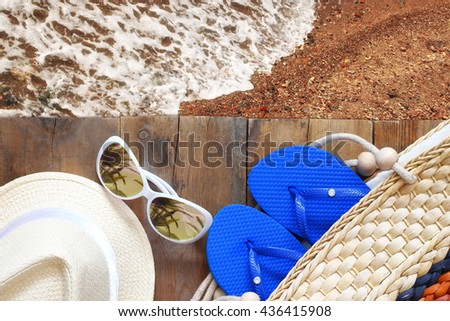 top view of sea sand and wooden deck with beach accessories   - stock photo