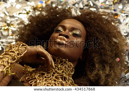 Top view of sensual attractive young woman with gold lips sending air kiss and lying on background shining confetti - stock photo