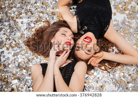 Top view of sensual attractive young women with red lips posing and lying on background of shining confetti - stock photo