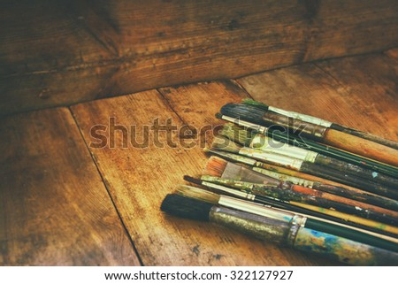 top view of set of used paint brushes and palette over wooden table