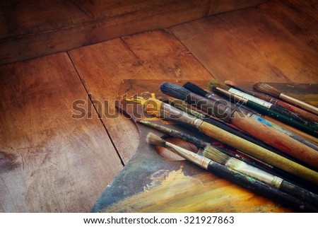top view of set of used paint brushes and palette over wooden table. retro filtered image