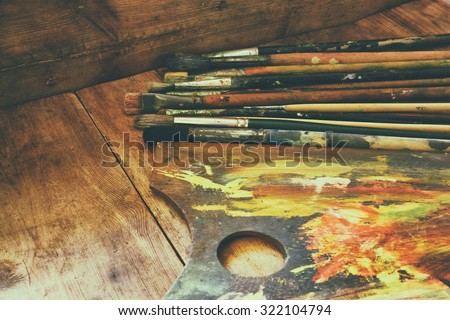 top view of set of used paint brushes and palette over wooden table. retro filtered image  - stock photo
