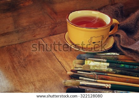 top view of set of used paint brushes, cup of hot tea and palette over wooden table  - stock photo