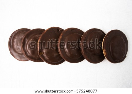 Top view of several chocolate covered snack cakes on a white background.
