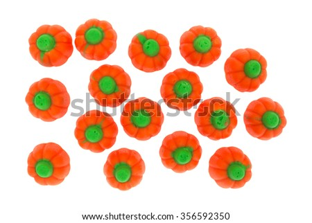 Top view of several pieces of orange and green Halloween pumpkin candy isolated on a white background. - stock photo