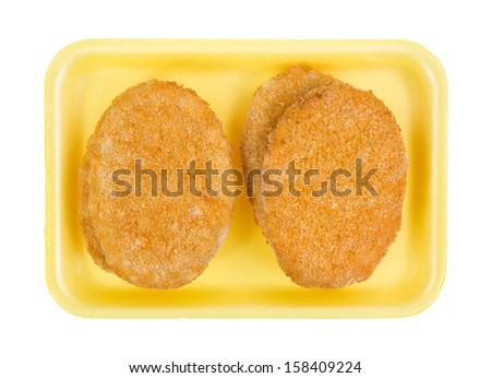 Top view of several pre-cooked frozen veal patties on a yellow butchers tray. - stock photo