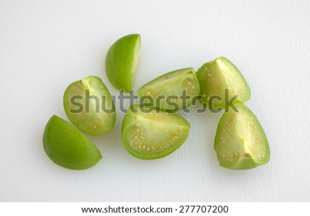 Top view of several sections of cut tomatillos on a white cutting board.