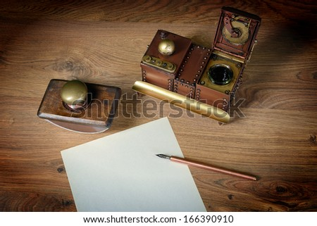 Top view of sheet of paper at wooden vintage desk. ink pen, inkstand with black ink and paperweight. - stock photo