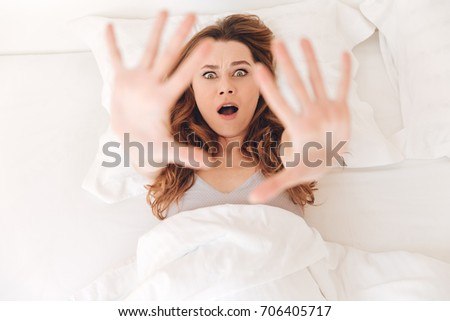 Top view of shocked young woman showing stop gesture while lying in bed in the morning