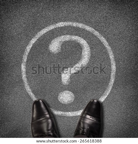 Top view of shoes standing on asphalt road with circle and question mark. Business concept - stock photo