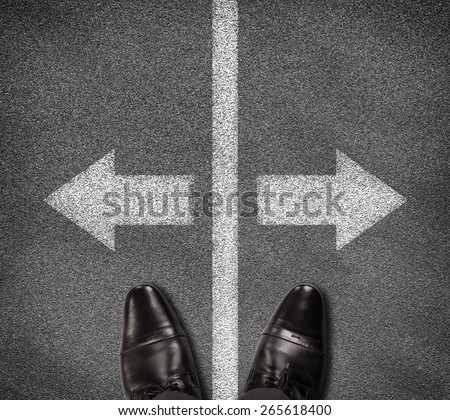 Top view of shoes standing on asphalt road with two arrows and vertical line. Business concept