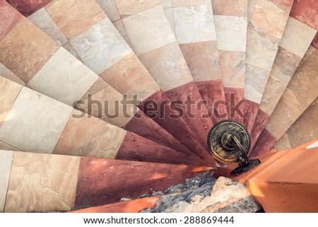 Top view of sidewalk lantern with stone spiral stairway - stock photo