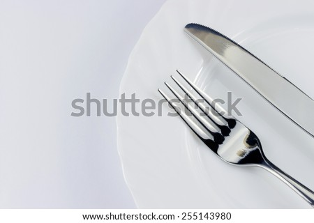 Top view of silver fork and knife on the plate over white background - stock photo