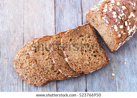 Top view of sliced fresh rustic wholemeal rye bread on a wooden table.