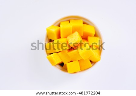 Top view of sliced ripe mango cubes in a white bowl on a white background.