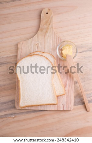 Top-view of slices bread with butter on wooden table - stock photo