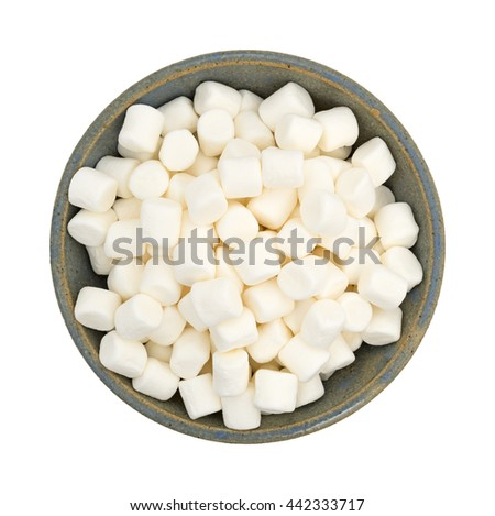 Top view of small bite size marshmallows filling an old stoneware bowl isolated on a white background.