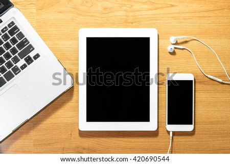 Top view of smart phone, laptop, tablet and earphone on wood table - stock photo