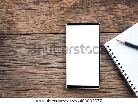 Top view of smartphone with white screen and gadgets on a wooden table background,vintage process style