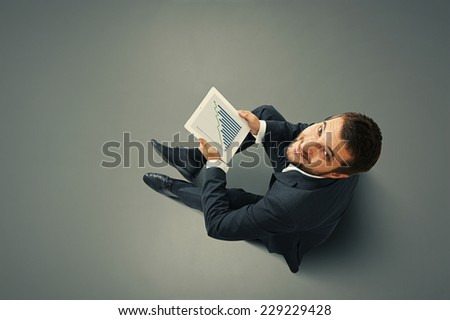 top view of smiley businessman holding touch pad with growing graph - stock photo
