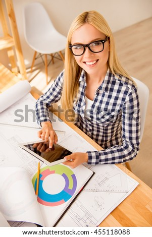 Top view of smiling engineer in glasses using tablet - stock photo