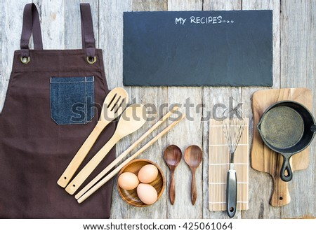 top view of some cooking utensils with black granite board for text on wooden background - stock photo