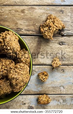 Top view of some delicious Italian cookies named ugly but good in a bowl and on rustic wooden table