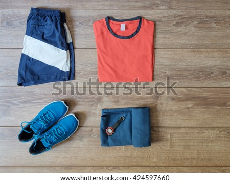 top view of sportswear clothes isolated on wooden background - stock photo