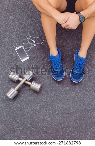 Top view of sporty man sitting on the floor of fitness center with dumbbells and smartphone with earphones in the foreground - stock photo