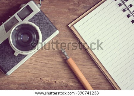Top view of stationery and camera on old wood table - stock photo