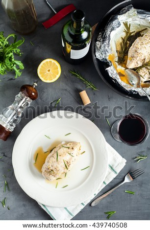 Top view of steamed in foil chicken breast with rosemary and spinach. Served with red wine. Grey stone background with glass, bottle, pepper mill and black pan with chicken. - stock photo