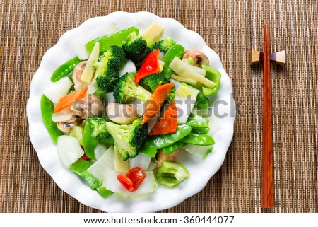 Top view of steamed mixed vegetables in large plate with bamboo mat underneath.