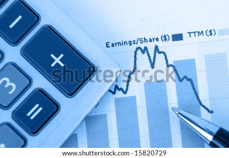 top-view of stock graph - focus is on graph with pen and calculator in foreground - stock photo