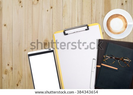 Top view of stuff office desktop and copy space. Analyze data chart show on paper and tablet, planner notebook, glasses and coffee.  - stock photo