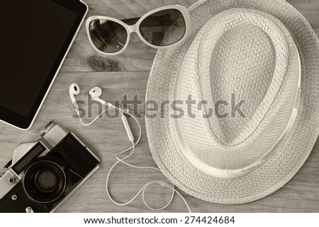 top view of stylish hat woman sunglasses old camera and tablet device over wooden table. black and white photo. vacation and travel concept - stock photo