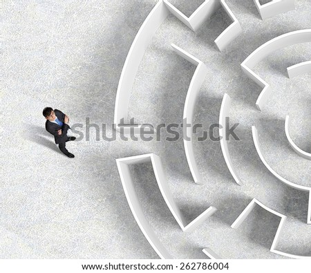 Top view of successful businessman standing near the entrance of labyrinth - stock photo