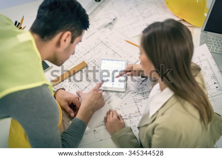 Top view of successful young architects checking the architectural plans on tablet in the office. - stock photo