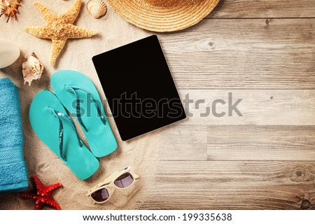 Top view of summer accessories and blank tablet on wooden planks - stock photo