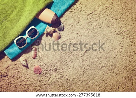 Top view of summer accessories on sandy beach - stock photo