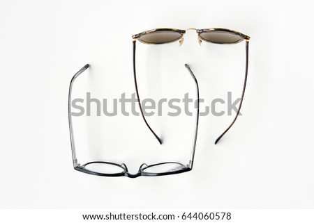 Top view of sunglasses and reading glasses on white background. Represents work and vacation