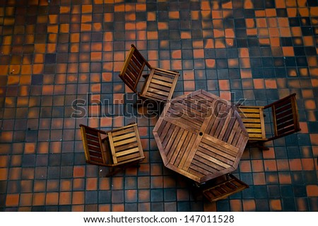 Top view of table and four chairs with a checkered floor in the background. - stock photo