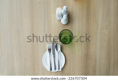 top view of table setting with glass and plate in restaurant - wood background  - stock photo